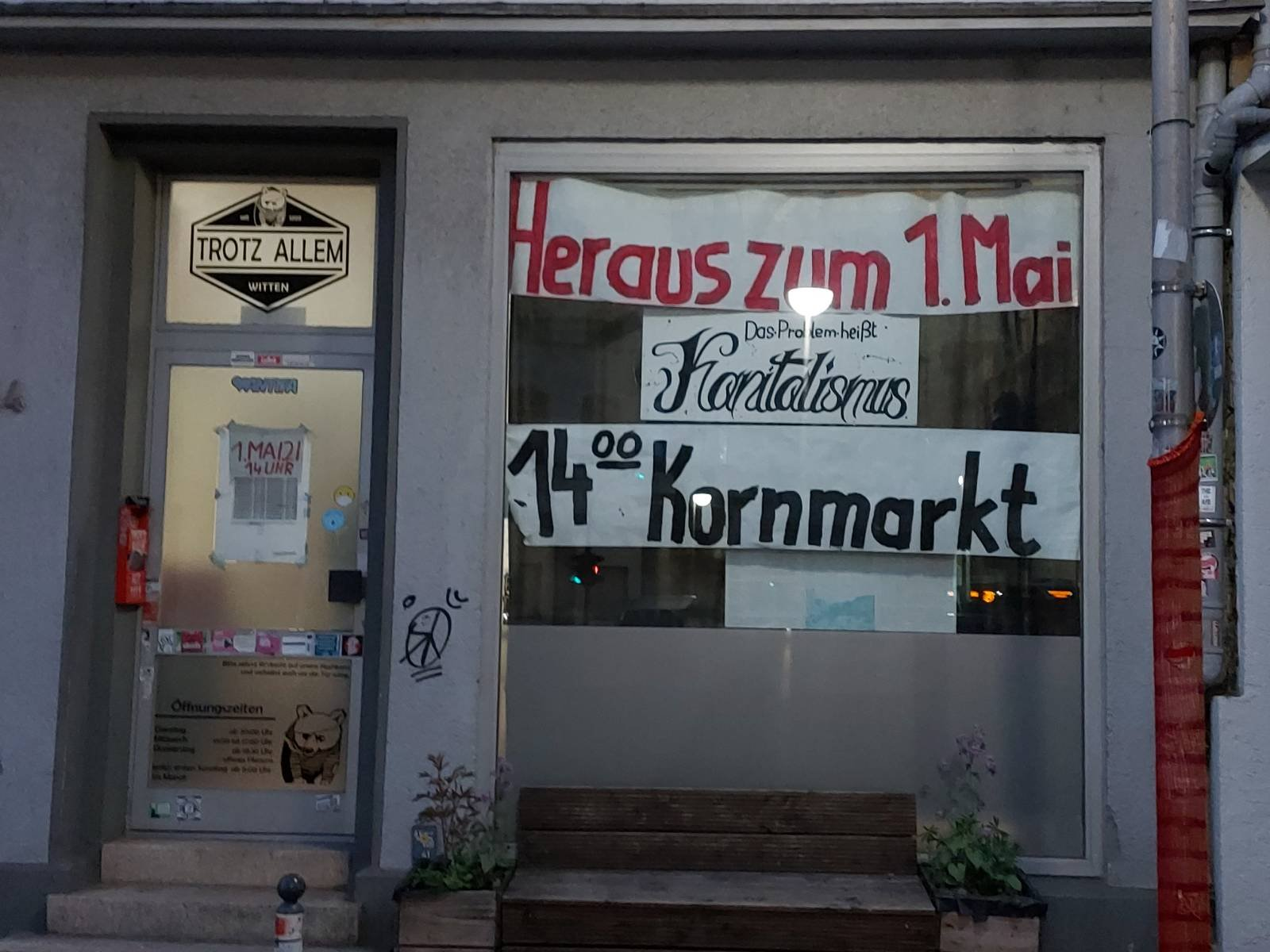 """Schaufenster des Trotz Allem mit Schriftzug """"Heraus zum 1. Mai – Das Problem heißt Kapitalismus – 14:00 Uhr, Kornmarkt"""""""